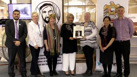 Image of ANU Library staff with representatives from the United Arab Emirates Embassy, presenting book collection.
