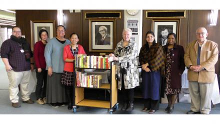 A group of people stand, smiling at the camera, surrounding a small trolley which has a few dozen books on it.