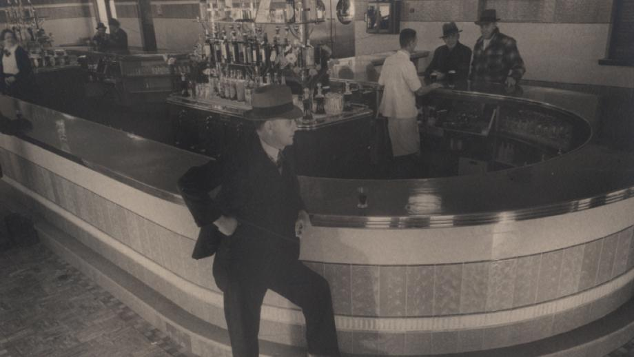 A historical photo of a man standing at the bar of a pub