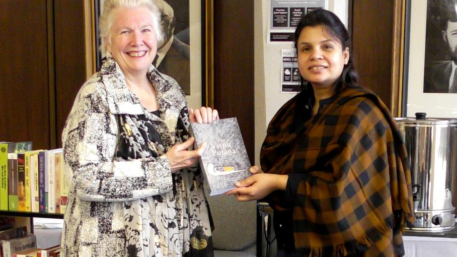 Two people smile at the camera and hold a book. Giving the book is Ruchika Jain from the High Commission of India, Canberra. Receiving the book is Roxanne Missingham, Unviersity Librarian at the Australia National University